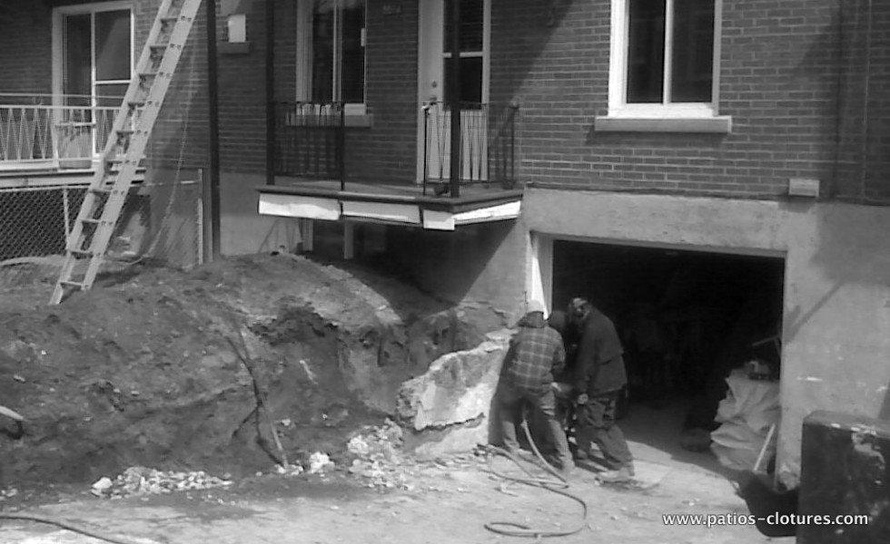 Démolition d'un mur de béton pour bâtir un patio au dessus du stationnement