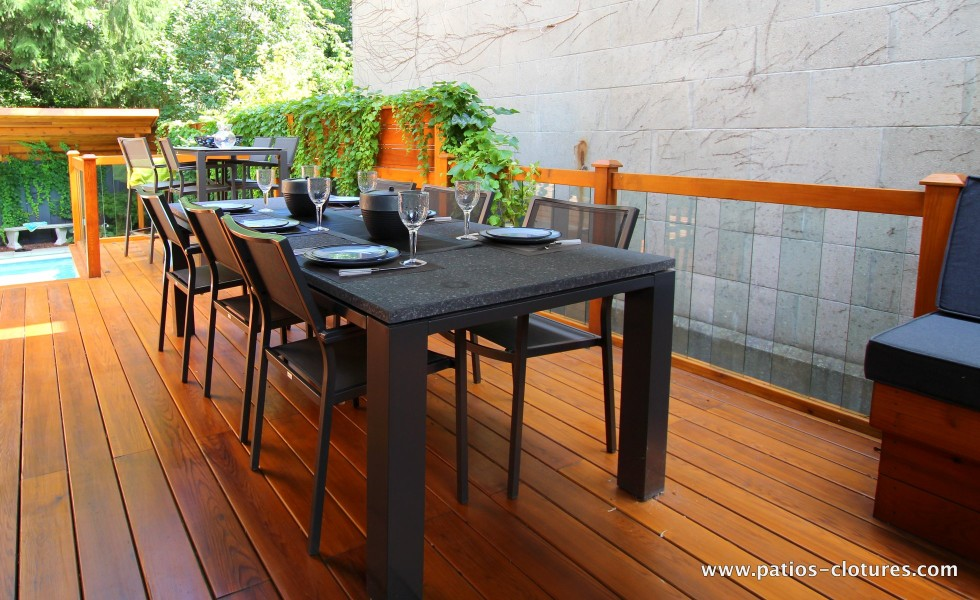 Dining area with table for 6 to 8 people and railing with tempered glass panels. The deck floor is red cedar without knots.