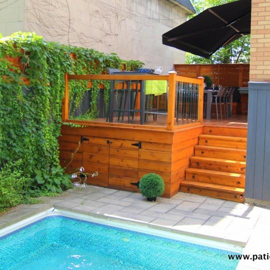 Vue du patio du côté piscine montrant le coin bistro, la rampe de verre trempé et l'escalier encastré.