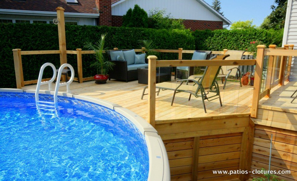 Large pool deck for an above ground pool and glass railing