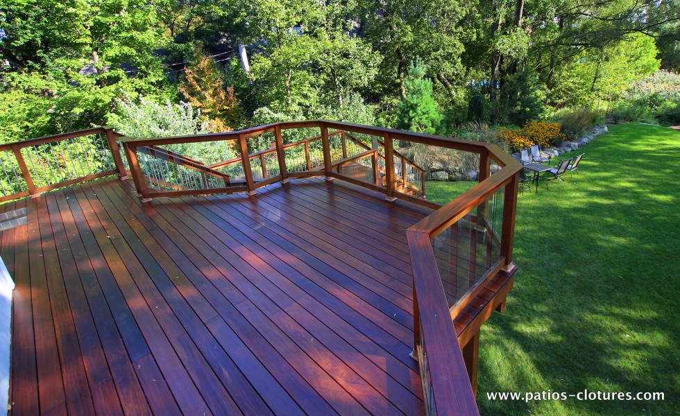 Large dining area on a balcony with ipe flooring and tempered glass railing