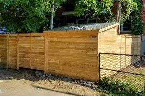 Cabanon en cèdre intégré à la clôture montrant sa toiture en acier galvanisé (projet Guérard)