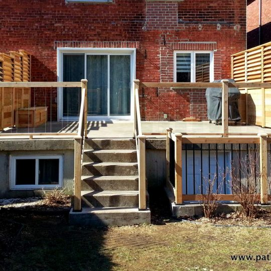 Concrete deck with cedar privacy screens and tempered glass railing