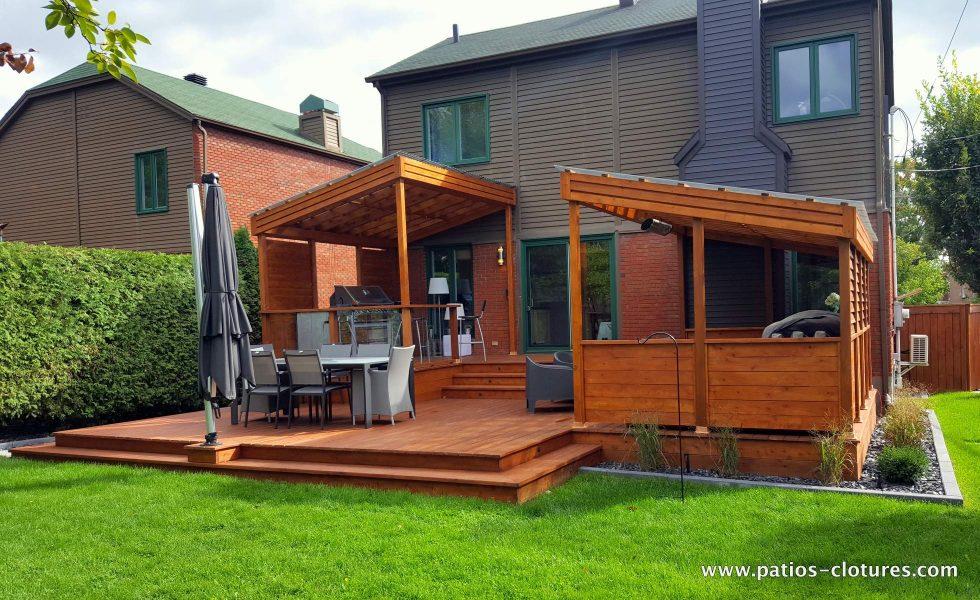 Vue de côté du patio Sylvie montrant le grand espace repas avec parasol à mat décentré, le coin-lounge couvert et intime et l'espace BBQ également couvert.