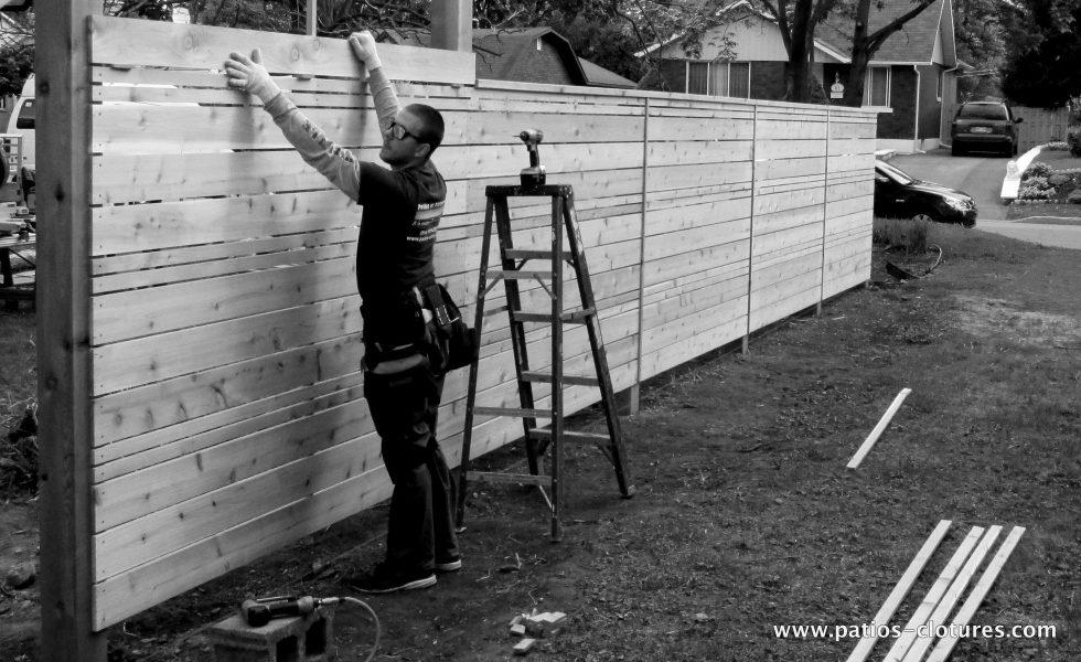 construction d'une clôture horizontale en cèdre ajourée avec alternance