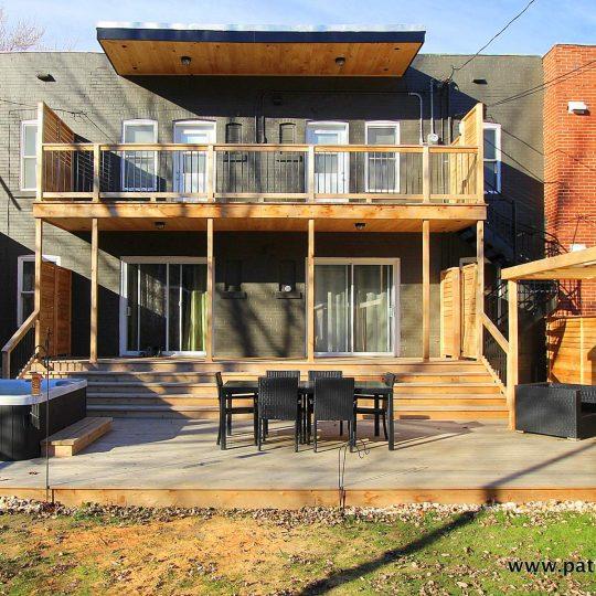 Vue de face. Remplacement des balcons par deux nouveaux balcons, un escalier colimaçon en aluminium, une terrasse basse incluant un spa, une espace repas et un coin lounge avec pergola. Patio Gendron.