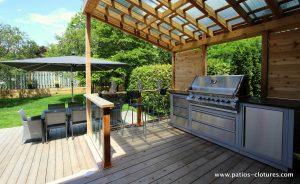 L'espace BBQ couvert du patio Sylvie. La rampe avec paneaux de verre trempé sert également de comptoir de service.