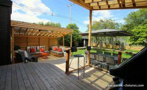 Vue de l'intérieur de l'espace BBQ couvert du patio Sylvie montrant l'espace repas et le coin-lounge.