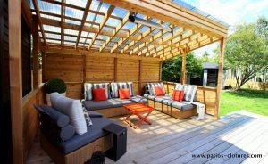 Coin-lounge avec un toit transparent et un écran d'intimité avec volets. Un système de chauffage radiant électrique permet de profiter de cet espace extérieur durant les soirées fraîches. Pour plus d'information sur les systèmes de chauffage radiant extérieurs visitez https://www.patios-clotures.com/chauffage-pour-patios-en-bois