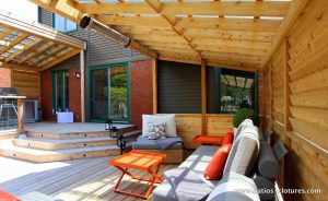 Vue de l'intérieur du coin lounge du patio Sylvie montrant le système de chauffage radiant. Pour plus d'information sur les systèmes de chauffage radiant extérieurs visitez https://www.patios-clotures.com/chauffage-pour-patios-en-bois