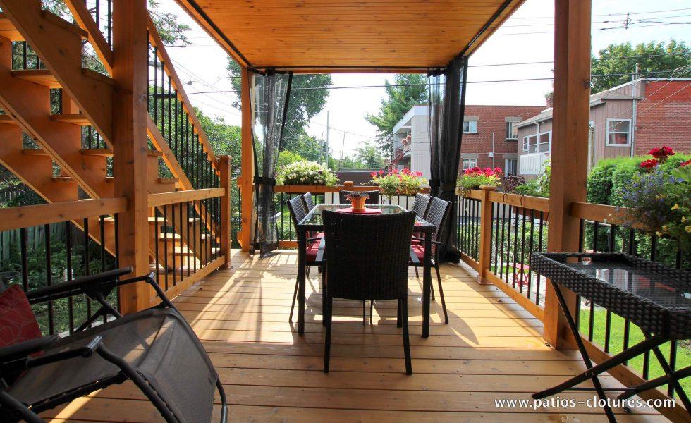 Premier niveau du patio à deux étages Chartré. Plafond en pin embouveté. Moustiquaires sur mesure. Escalier droit en cèdre à deux palliers.