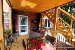 Vue de la porte extérieure menant au niveau du bas du patio à deux étages Chartré. Plafond en pin embouveté. Moustiquaires sur mesure. Escalier droit en cèdre à deux palliers.