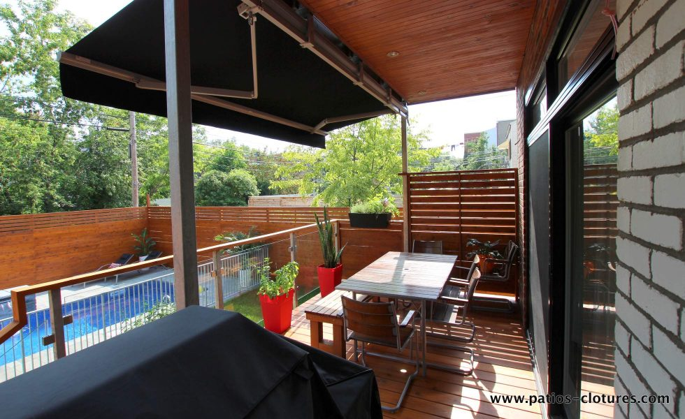 Vue de l'espace repas intime près de la porte patio. La rampe de verre trempé avec poteaux d'acier galvanisé permet de bien voir se qui se passe dans la piscine en tout temps. (Projet Rigal)