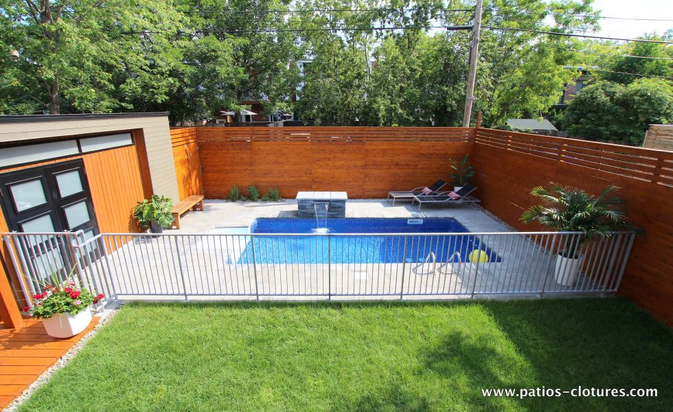 Inground pool surrounded by a cedar fence and a galvanized steel fence. (Rigal project)