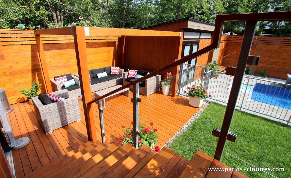 Tempered glass railing with galvanized steel posts topped with a cedar handrail. (Rigal project)