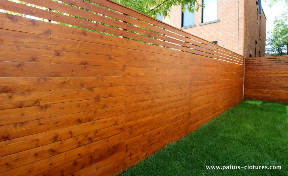 Fence horizontal palisade cedar type continuous (posts visible next door) with small planks spaced at the top. (Rigal project)