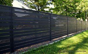 distingué au travers d'une clôture horizontale en bois foncé ajourée avec alternance