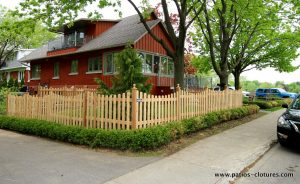 """""""Picket fence"""" cedar fence with curved sections. View of the street."""