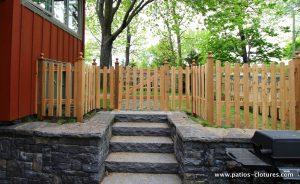 """Haut de l'escalier en pierre. Porte de clôture en cèdre modèle """"picket fence"""". Vue du stationnement."""