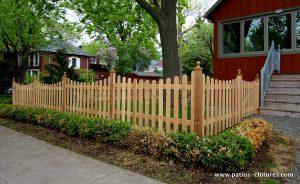 """Clôture modèle """"picket fence"""". Les planches des sections de la clôture sont coupées à différentes hauteurs pour donner un effet de vallons."""