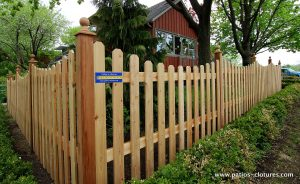 """""""Picket fence"""" cedar fence with curved sections. View at the corner near the sidewalk."""