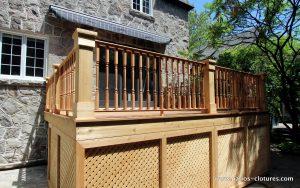 Side view. Deck with an Ipe wood floor, colonial style cedar railings and traditional cedar lattice skirt in frames. Patio deck Labadie.