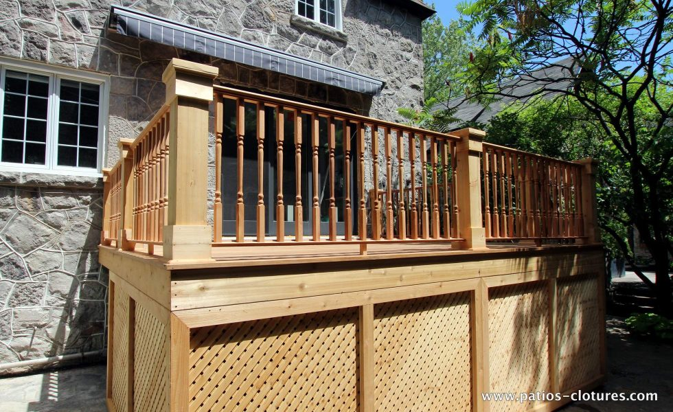Side view. Deck with an Ipe wood floor, colonial style cedar railings and traditional cedar lattice skirt in frames. Patio deck Labadie.