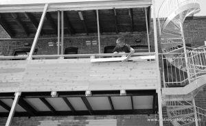 Nick durant l'installation des planches du garde corps en cèdre du deuxième étage. (Projet Rigal)