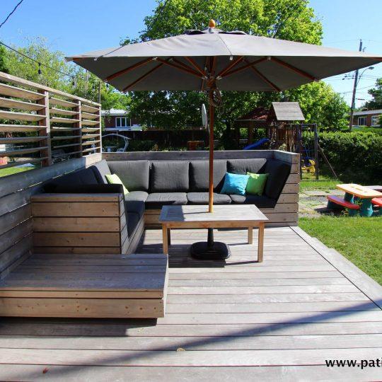 Coin divan sur mesure du patio Blanchette et un écran d'intimité avec persiennes mobiles. Le plancher du patio est en ipé. Il a été laissé à l'état brut et le soleil l'a fait pâlir lui donnant une belle couleur grise argentée. Pour en savoir davantage sur le bois ipé gris, visitez https://www.patios-clotures.com/grisonner-le-bois-ipe-de-votre-terrasse-pour-un-look-naturel-tendance