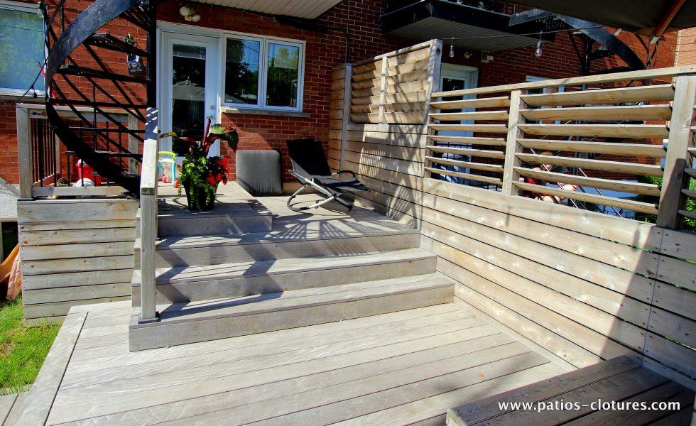 Balcon d'accès du patio Blanchette montrant également l'écran d'intimité avec persiennes mobiles. Le plancher du patio est en ipé. Il a été laissé à l'état brut et le soleil l'a fait pâlir lui donnant une belle couleur grise argentée. Pour en savoir davantage sur le bois ipé gris, visitez https://www.patios-clotures.com/grisonner-le-bois-ipe-de-votre-terrasse-pour-un-look-naturel-tendance