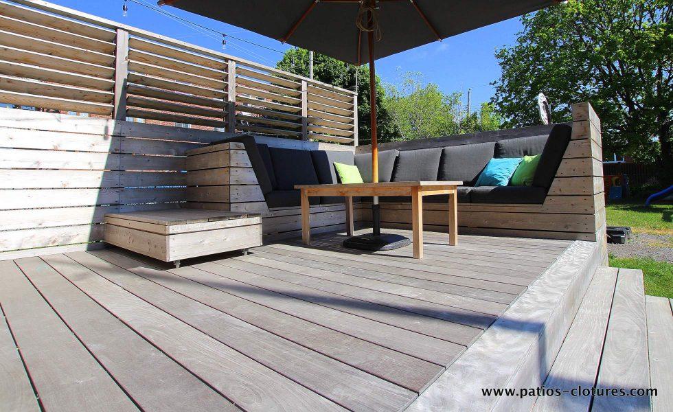 Plancher en ipé et coin divan du patio Blanchette. Le bois ipé du plancher est à l'état brut et le soleil l'a fait pâlir lui donnant une belle couleur grise argentée. Pour en savoir davantage sur le bois ipé gris, visitez https://www.patios-clotures.com/grisonner-le-bois-ipe-de-votre-terrasse-pour-un-look-naturel-tendance