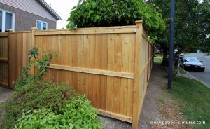 Fence in cedar wood, intimate, vertical planks. View of the street side.