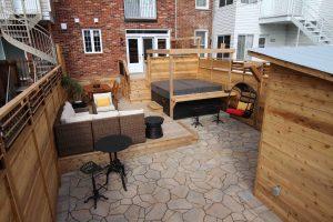 Cour avec spa, lounge, espace repas, cuisine extérieure, chaises suspendues, stationnement et cabanon intégré à la clôture (projet Brouillette)