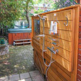 Patio avec douche extérieureinstallée derrière la rampe (patio Sjroi)