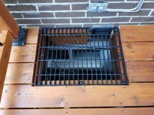 Patio avec une grille métallique au dessus d'une fenêtre du sous-sol sous le patio (Patio Lagarde)