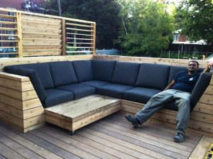 Un rangement en bois intégré à une banquette sur mesure pour optimiser l'espace disponible sur le patio (patio Blanchette)