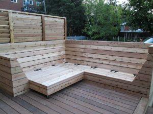 Un rangement en bois intégré à une banquette sur mesure pour optimiser l'espace disponible sur le patio