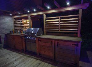 Patio avec BBQ près de la porte, accessible facilement avec des comptoirs et un écran d'intimité. Il s'éclaire le soir venu pour une ambiance chaleureuse (patio Legault)