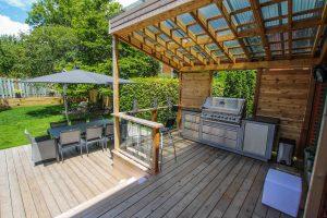 Patio avec BBQ près de la porte, comptoir de service, écran d'intimité et toiture pergola recouverte de polycarbonate (patio Ayllon)