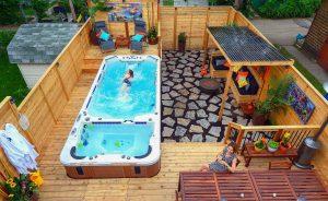 Patio en cèdre avec spa de nage intégré sur trois côtés (patio Vandal)