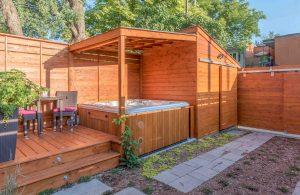 Patio en cèdre avec spa intégré recouvert d'un toit et adossé au cabanon (patio Daigle)