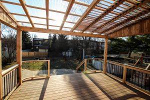 Pergola recouverte d'un toit en polycarbonate avec des persiennes mobiles positionnées entre les solives de la pergola pour mieux contrôler la luminosité (patio Pinet)