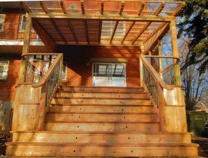 Patio avec pergola recouverte d'un toit en polycarbonate avec des persiennes mobiles positionnées entre les solives de la pergola pour mieux contrôler la luminosité (patio Pinet)