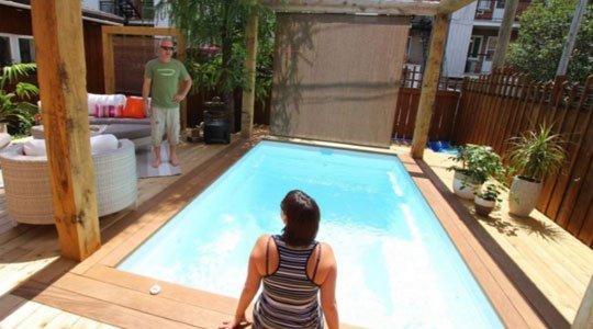 Patio avec une terrasse en cèdre et bordure en bois ipé autour d'une piscine creusée