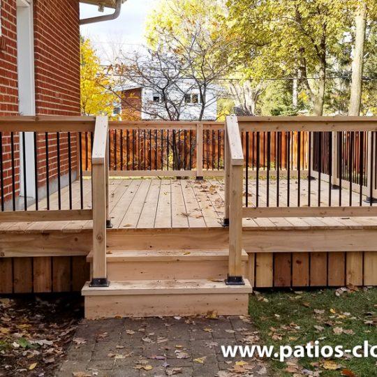 Patio un niveau classique en cèdre avec rampe de cèdre et barreaux en aluminium noir. Escalier de côté de 4' de large.